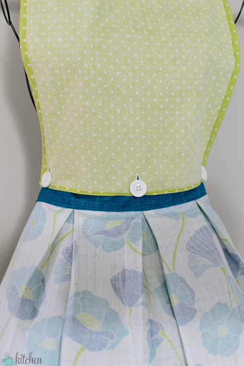Inside View of Apron: Buttons attach the top of the apron to the inside of the waistband. By unbuttoning the top, it can be removed and worn as a waist-length apron.
