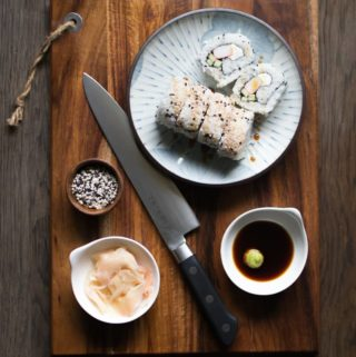 sushi rice, homemade sushi rolls on a plate, Japanese knife on cutting board, pickled ginger, wasabi and soy sauce
