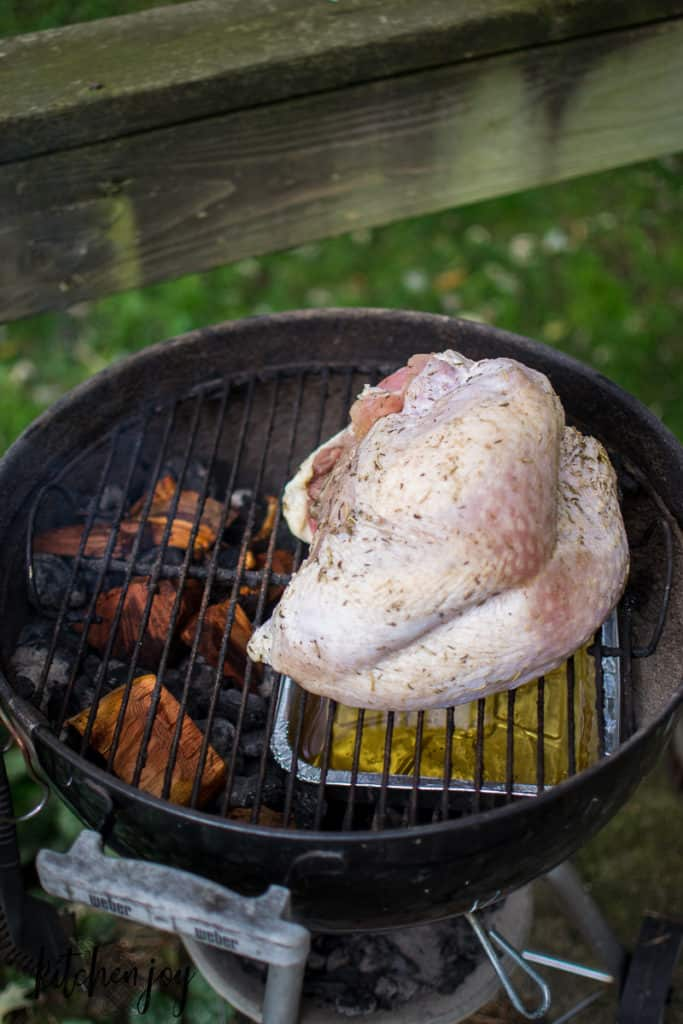 bone-in-turkey breast on a charcoal grill with wood for smoking