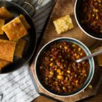beef chili with corn, tomato based chili in a bowl with cornbread
