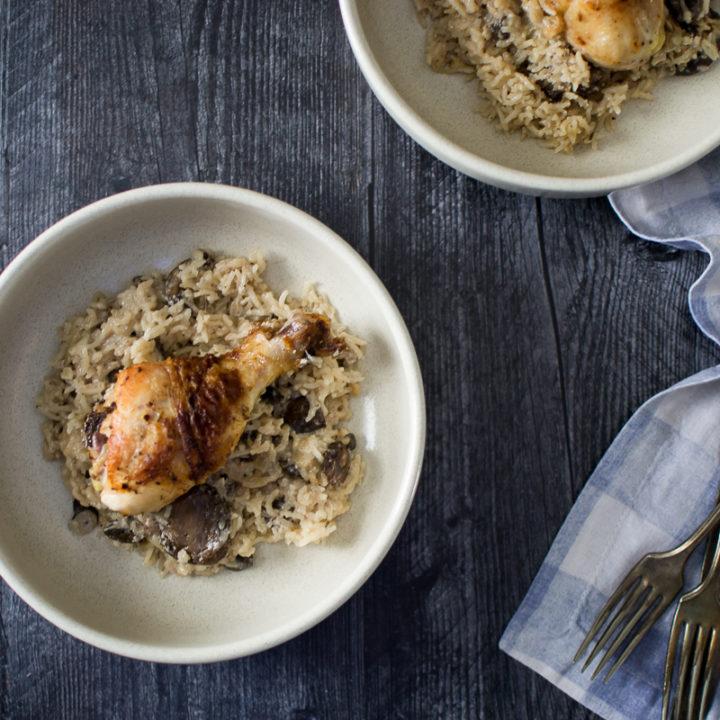 golden brown crispy skin chicken drumstick served on a bed ofcreamy mushroom rice