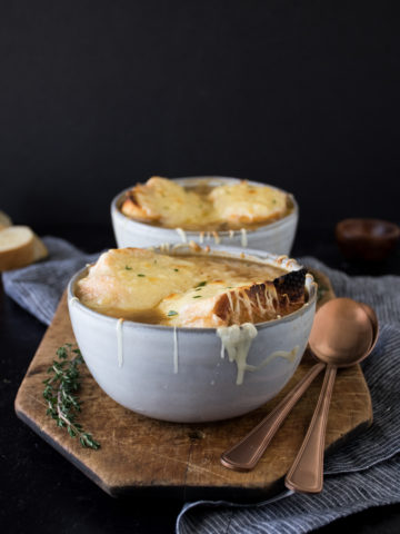 french onion soup with melted cheese on top in a gray bowl on a dark background