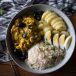 peruvian yellow pepper chicken served with potatoes, rice, hard boiled eggs, and olives in a large bowl