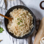 golden Peruvian Rice arrocito in a black bowl topped with cumin and chopped parsley