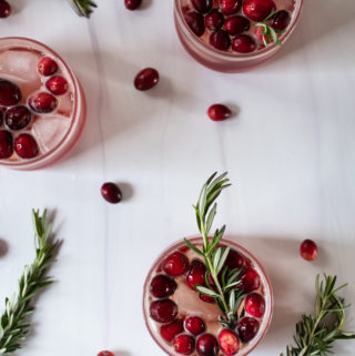 cranberry ginger gin fizz cocktails arranged on a white table topped with cranberries and fresh rosemary sprigs for garnish