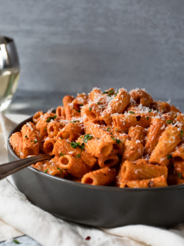rigatoni pasta coated in a vibrant, creamy tomato sauce topped with grated Parmigiano reggiano in a gray bowl