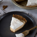 eggnog cream pie slice on dark plate, whipped cream on top of eggnog filling and gingersnap crust