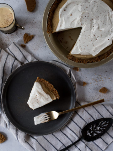 slice of eggnog cream pie on a dark plate with a bite missing, topped with whipped cream