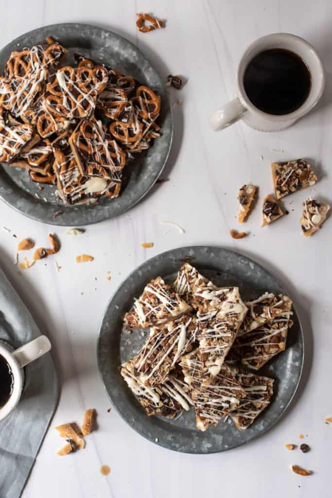 two trays of butter toffee topped with chocolate, pretzels, and pecans