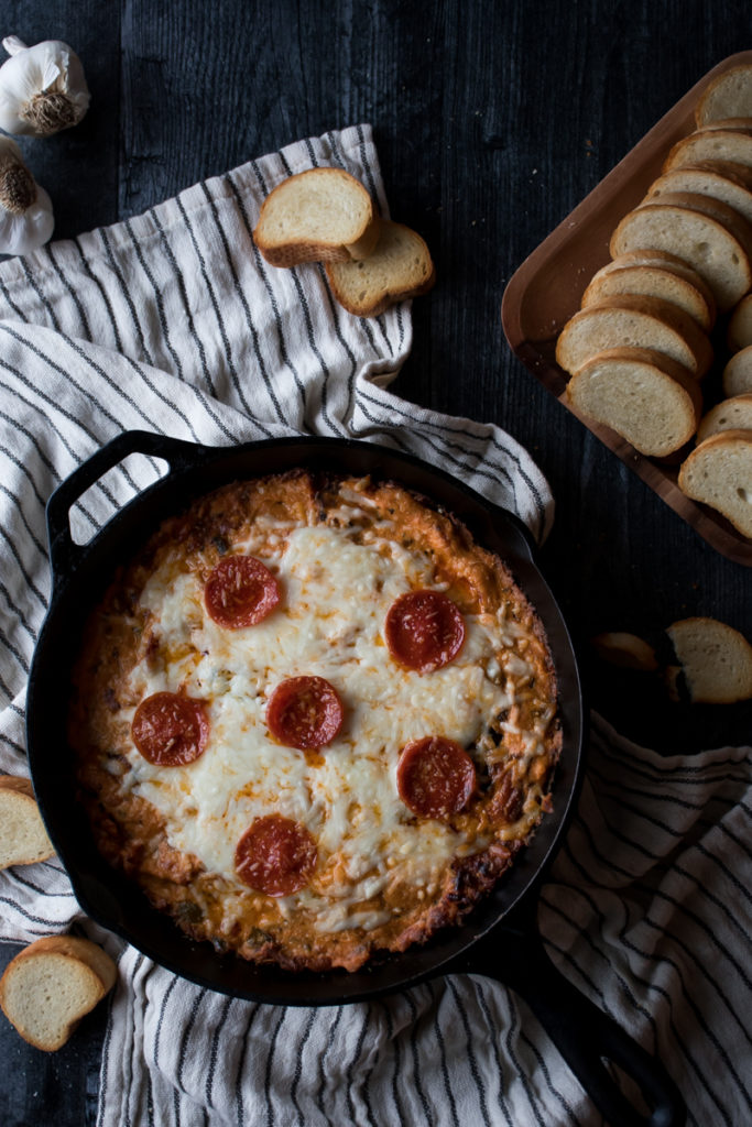cast iron skillet filled with hot pizza dip topped with pepperoni, served with a tray of toasted bread slices