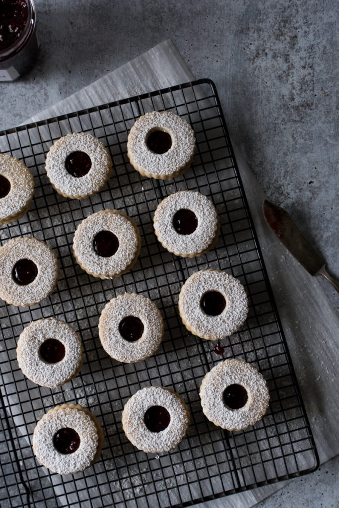 linzer cookies arranged on a cooling rack