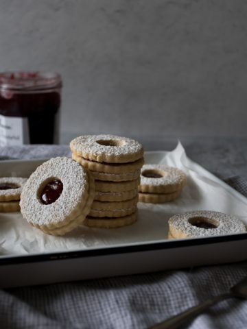 Stack of linzer cookies with raspberry jam in the center, dusted with confectioner's sugar