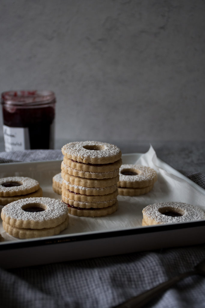 stack of linzer cookies on a tray with jam and powdered sugar
