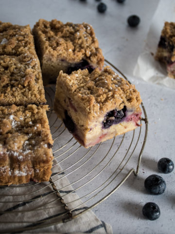 mixed berry crumb cake coffee cake cut into squares on a cooling rack