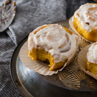 pumpkin sourdough cinnamon rolls with a bite out on a metal tray