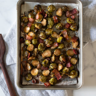 roasted brussels sprouts and bacon with balsamic glaze on a large sheet pan