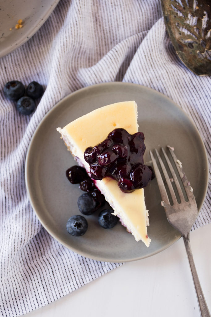blueberry swirl cheesecake slice served on gray plate with blueberry sauce on top
