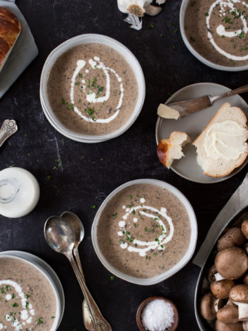 four bowls of creamy mushroom soup drizzled with cream and sprinkled with thyme